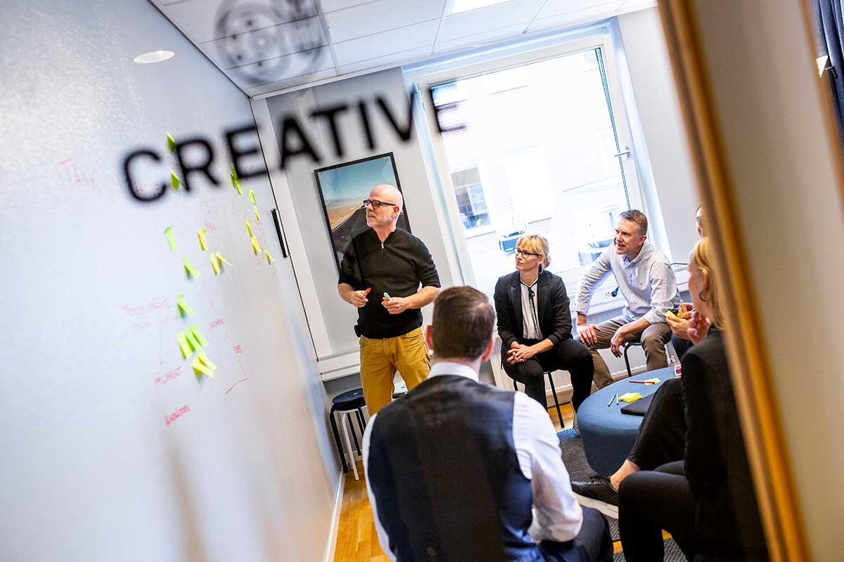 "En grupp personer har en workshop inne i ett mötesrum med texten ""creative"" på dörren"