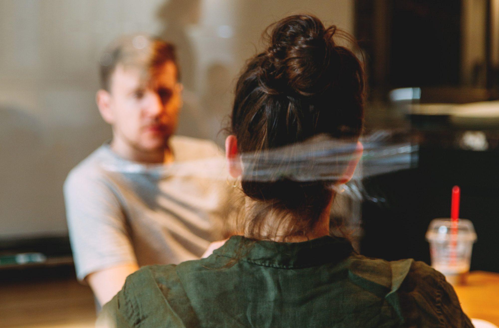 Två personer som samtalar bakom en glasvägg