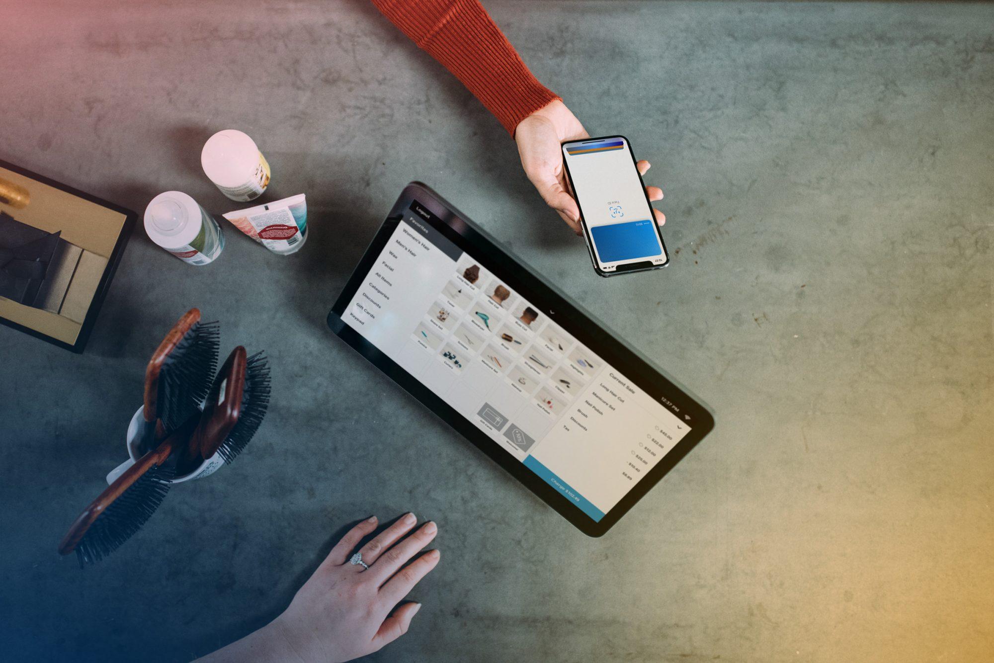 En surplatta, en telefon och händerna av två personer som genomför ett köp via e-handel.