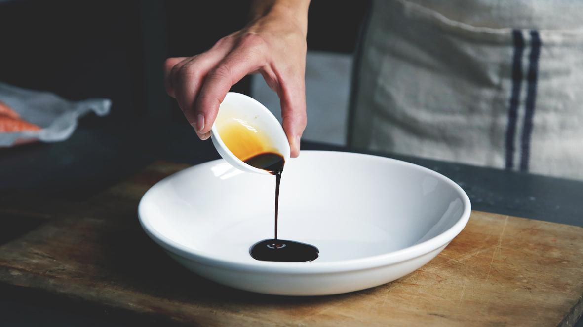Hand som häller upp mörk sås från en liten skål till en stor tallrik.
