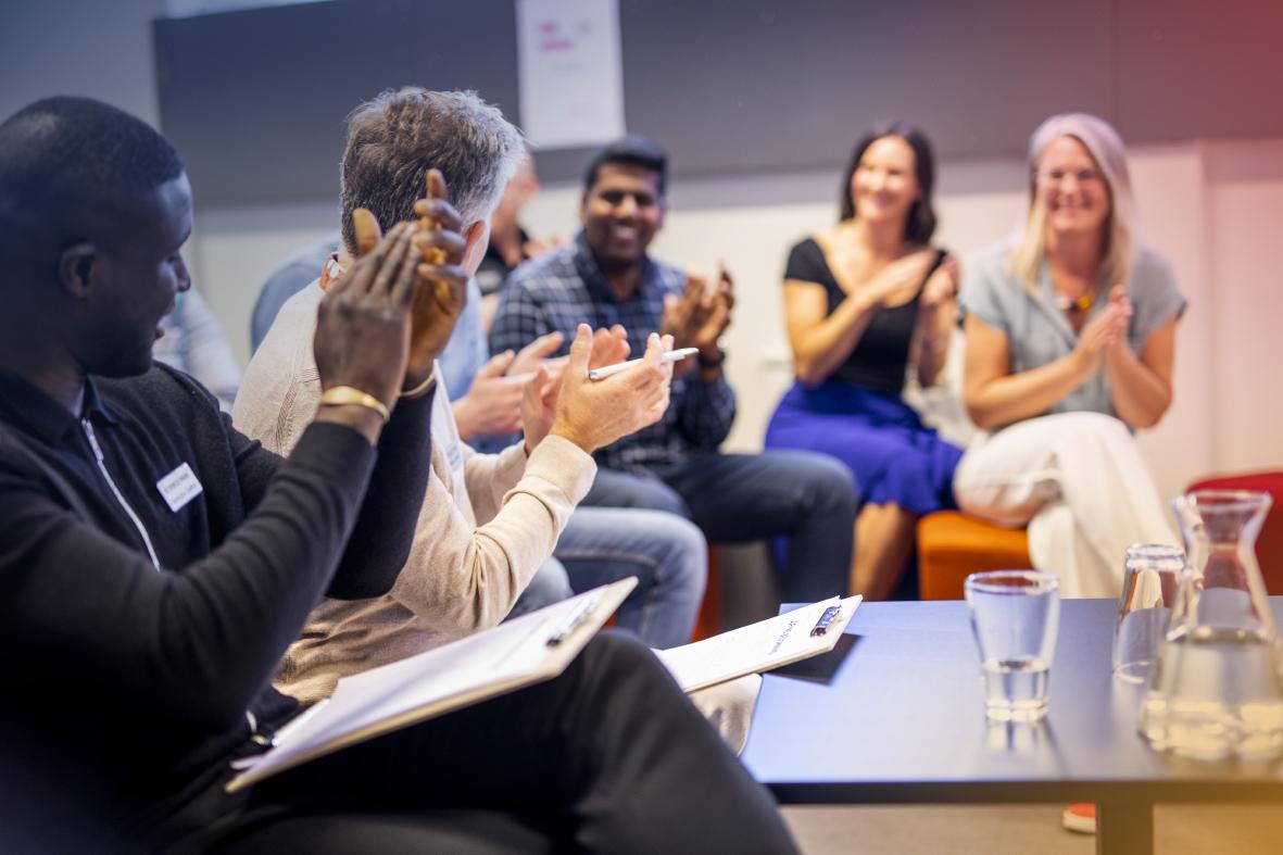 En grupp människor som applåderar glatt
