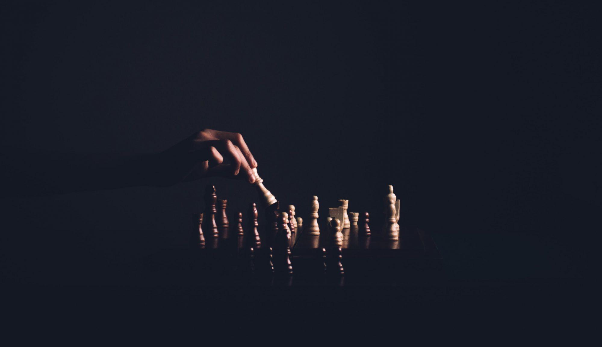 Uppställda schackpjäser och en hand som spelar