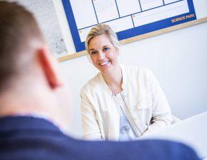 En man och en skrattande kvinna i mötesrum