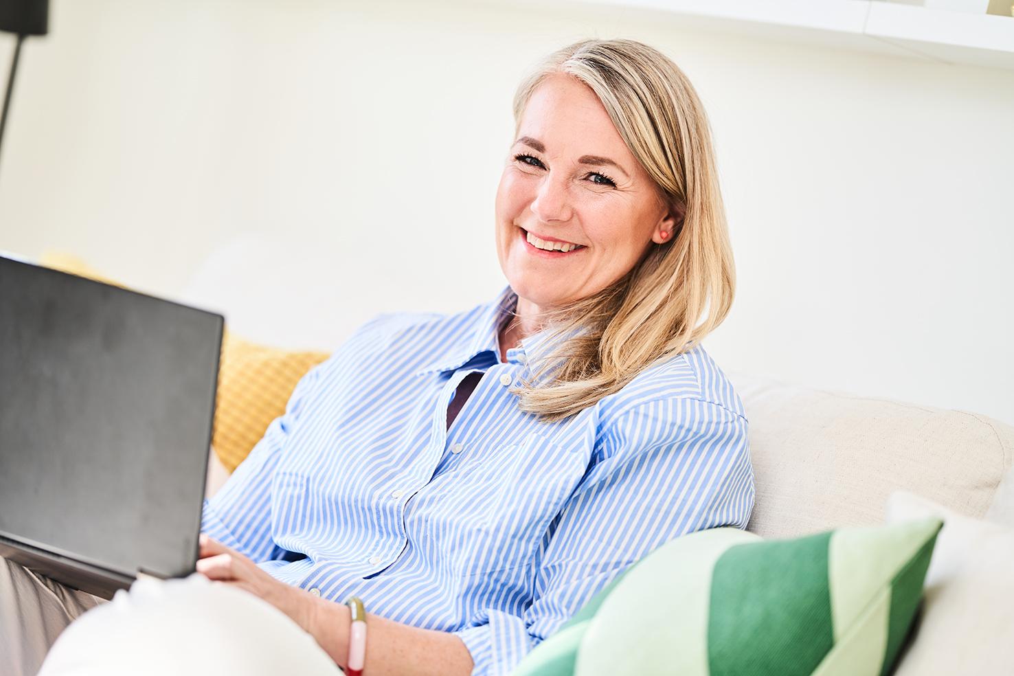 åsa juneström sitter uppkrupen i sin soffa med en laptop i knät