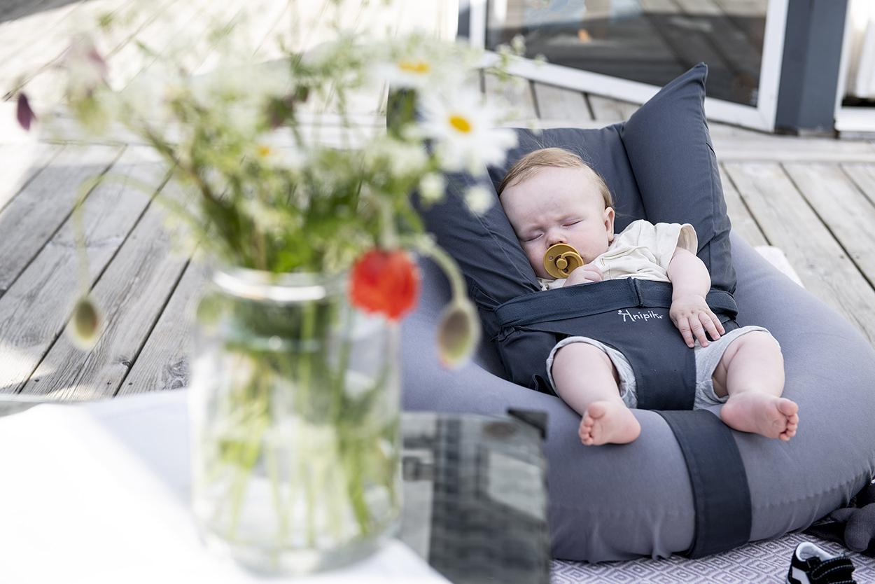 en bebis sover i den uppblåsbara babysittern knipik på en altan