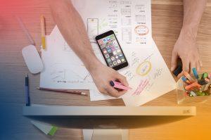 överblicksvy av skrivbord med en telefon och händer som antecknar med färgglada pennor