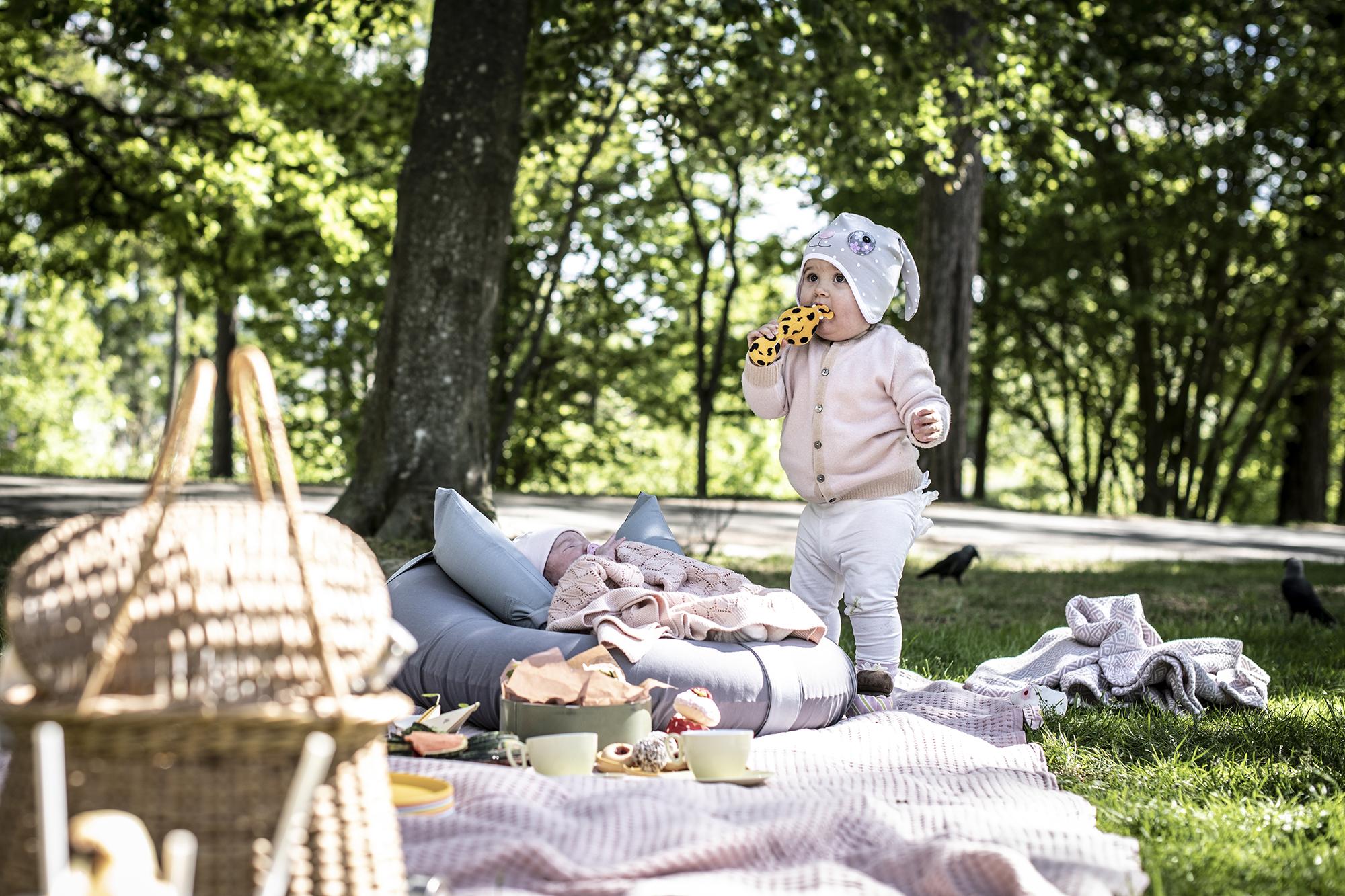 en bebis sover i den uppblåsbara babysittern knipik på en picknick medan syskonet leker bredvid