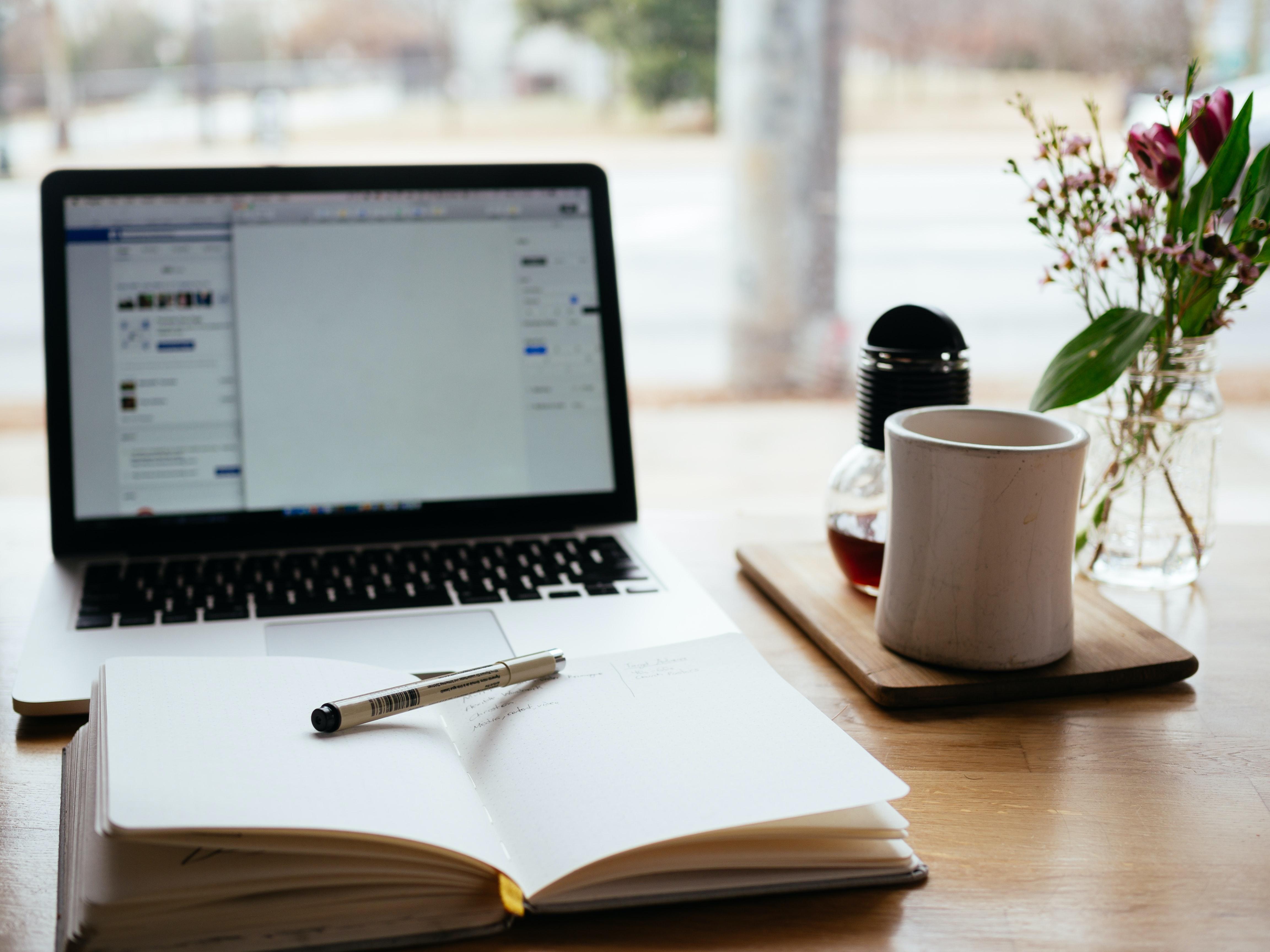 penna och anteckningsbok framför en laptop