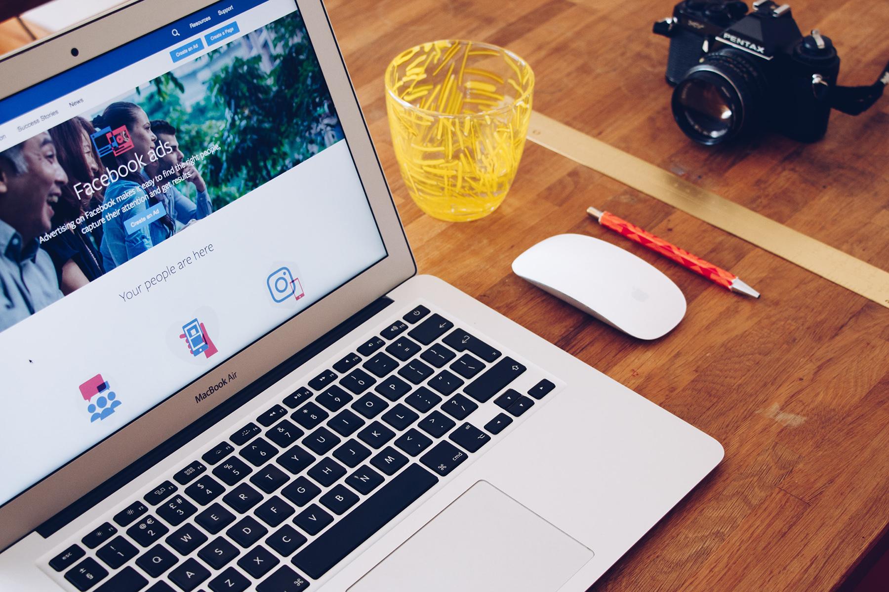 kamera, penna, glas och laptop med trådlös mus på skrivbord