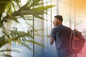 Ung kille med ryggsäck passerar glasdörrar ut från en byggnad.