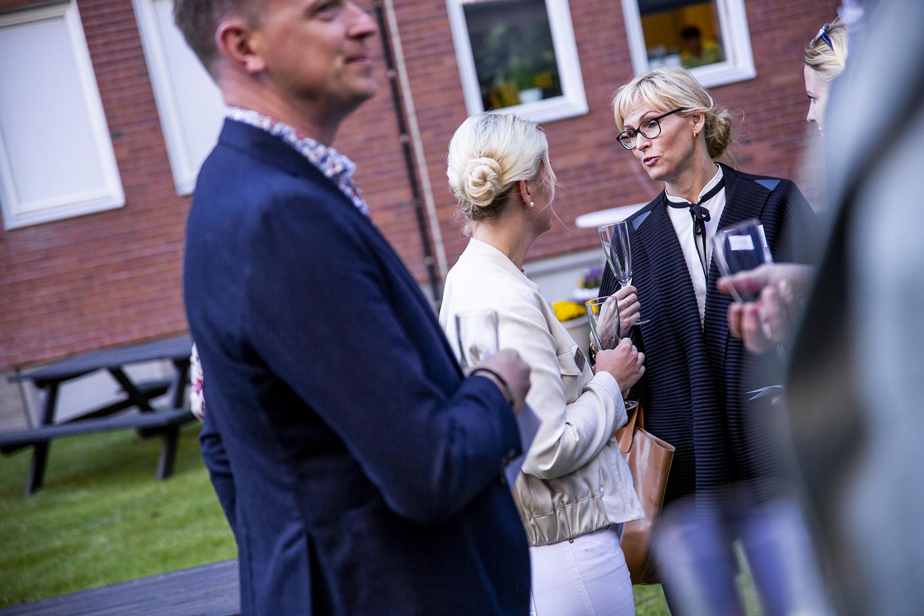 en man i förgrunden framför två blonda kvinnor som står utomhus och pratar