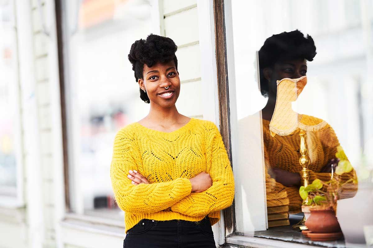 copywritern mary benadet står lutad mot en husvägg och tittar in i kameran