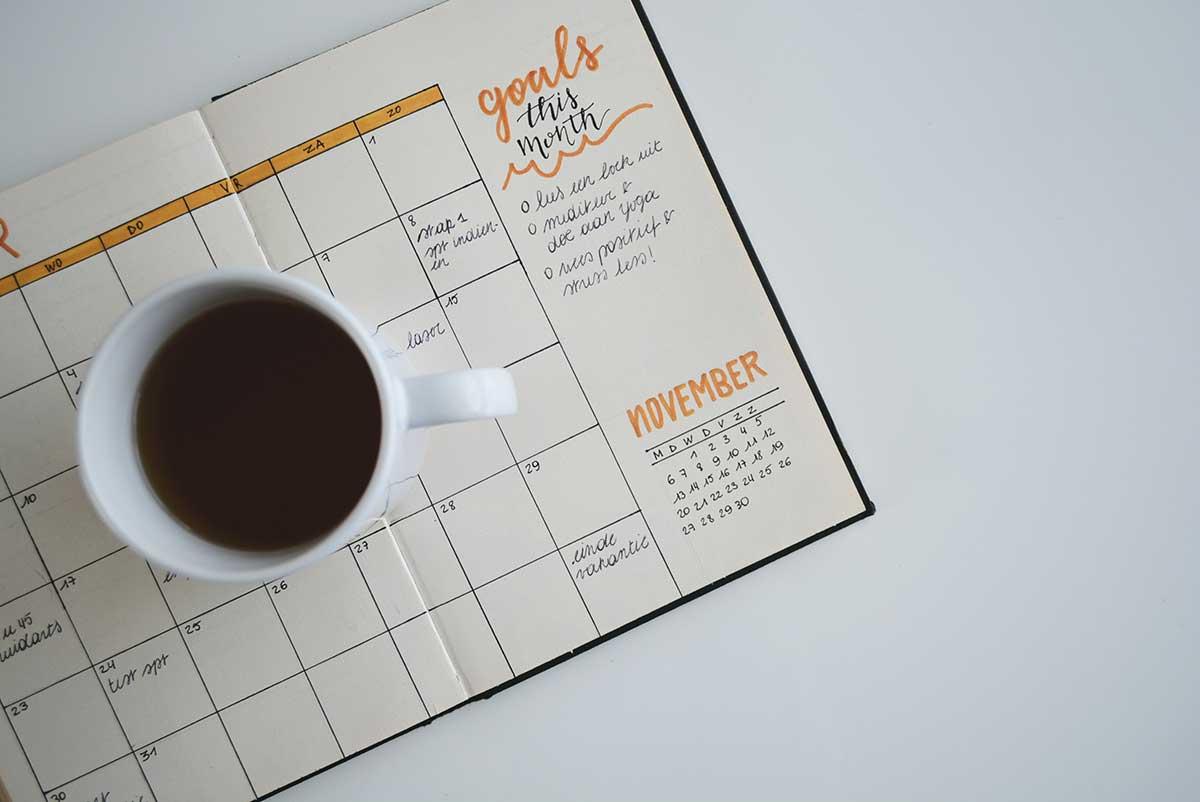 en kopp kaffe som står på en uppslagen kalender