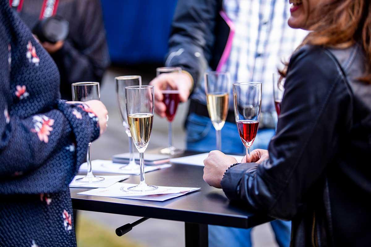 en grupp människor som står kring ett bord med champagneglas