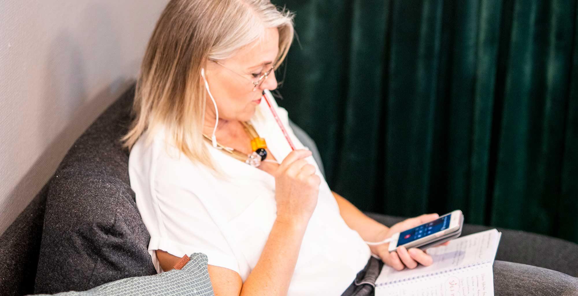 en kvinna sitter i en soffa och ringer ett samtal på sin smartphone
