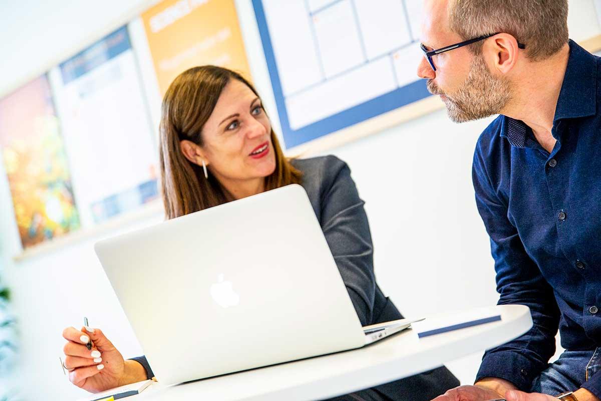en kvinna och en man sitter och pratar framför en laptop