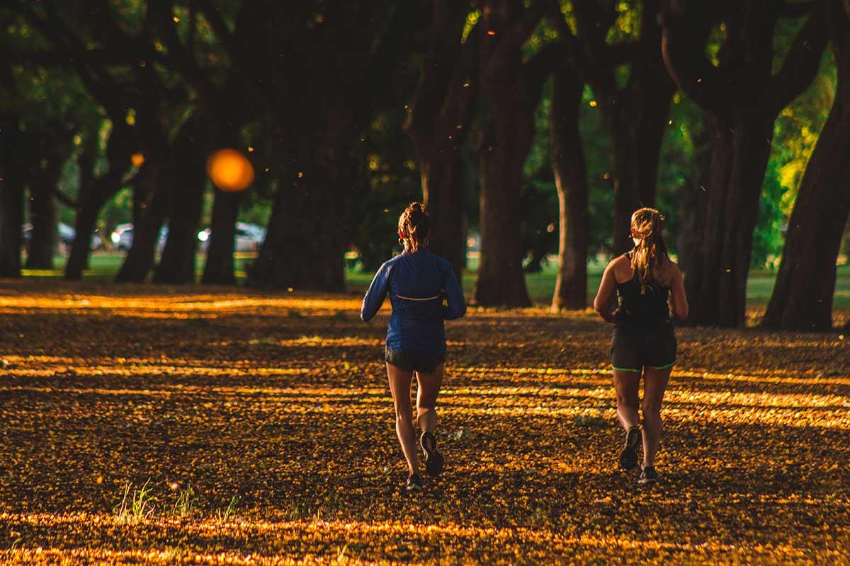 två personer joggar på en gata fylld av höstlöv