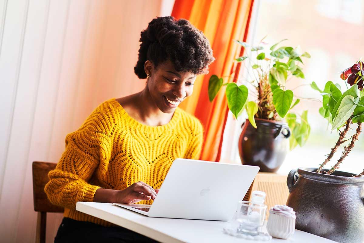 copywritern mary benadet sitter vid ett bord och skriver på sin laptop