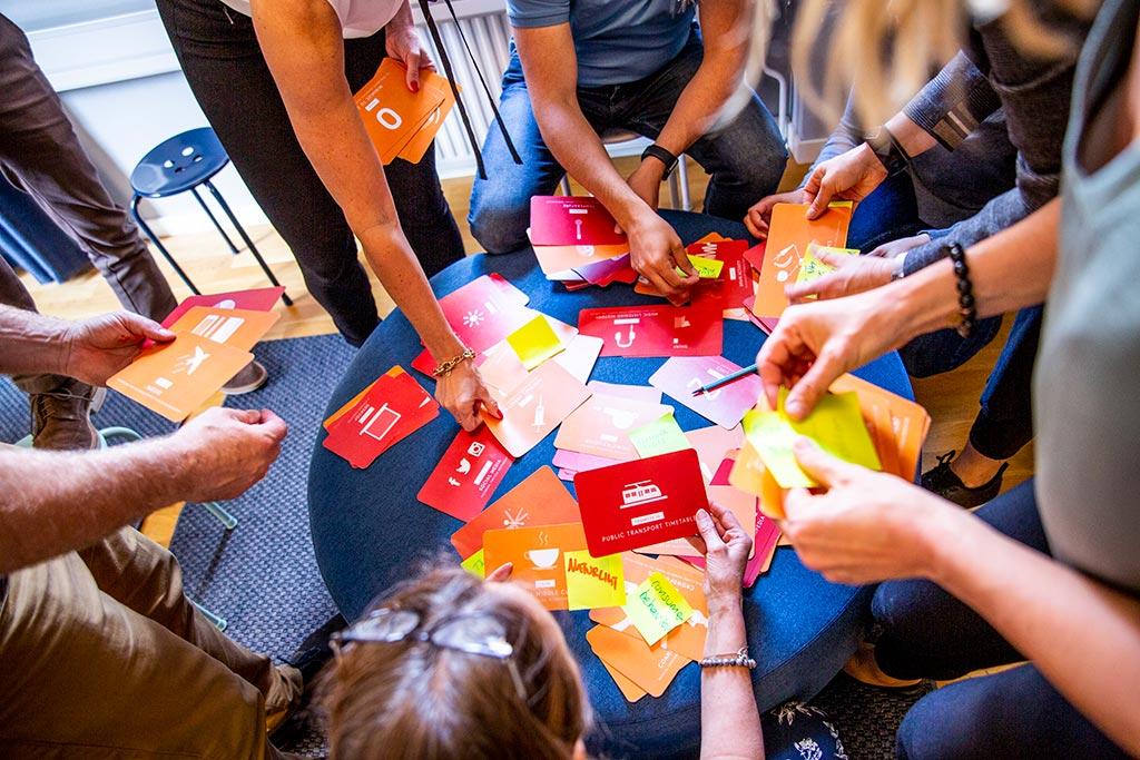 Ett bord i fågelperspektiv med händer som håller i kulörta kort med olika budskap och illustrationer.