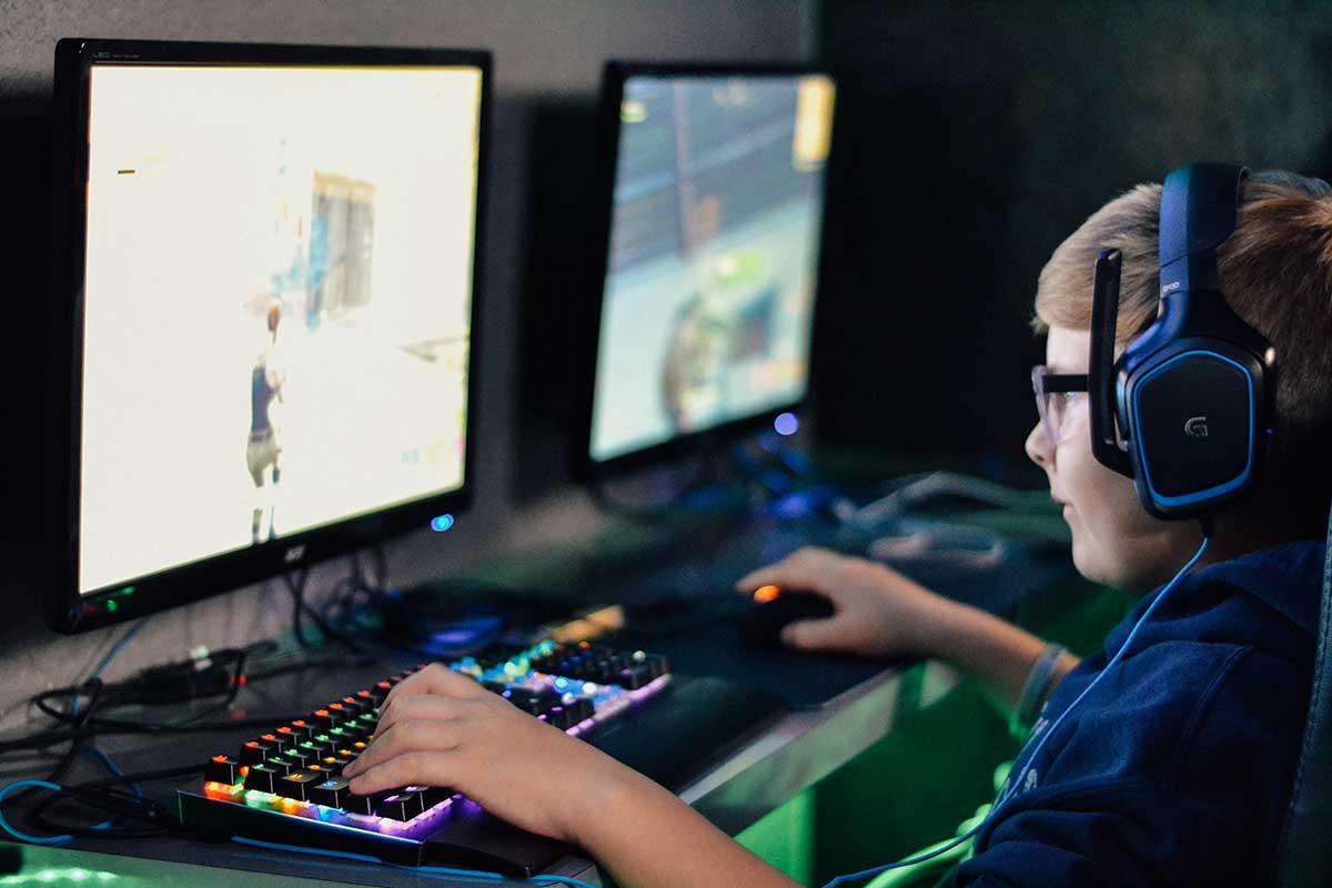 En pojke med glasögon sitter och spelar spel på dator med stor skärm