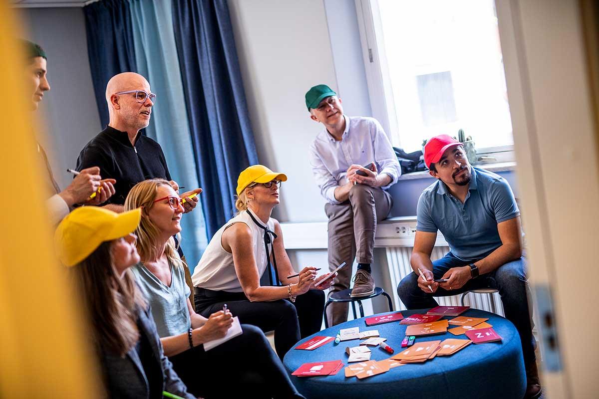 En grupp glada människor med olikfärgade kepsar och glasögon deltar i en workshop