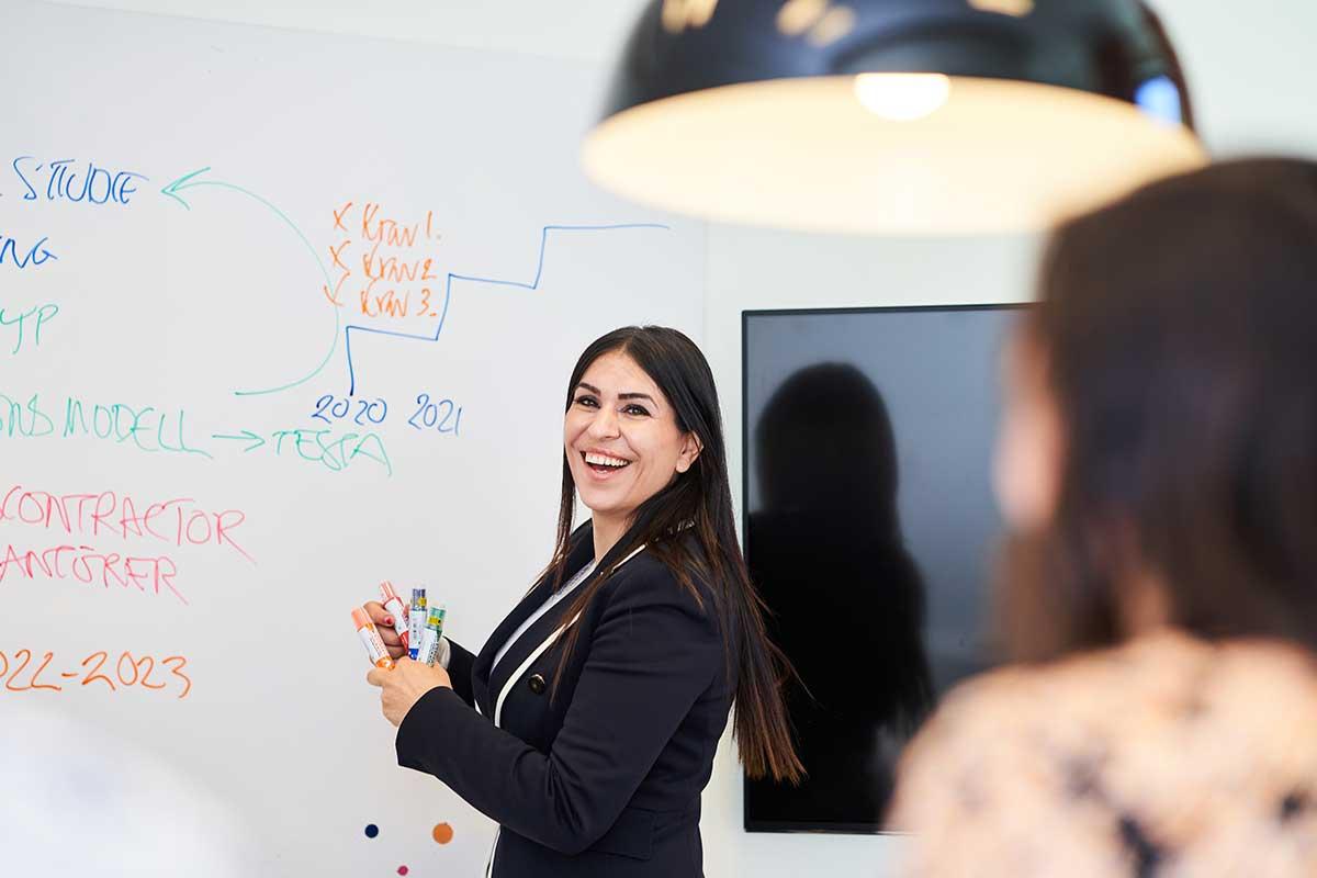 Entreprenören Miden Melle Hannah står leende framför en whiteboardtavla och håller i en presentation