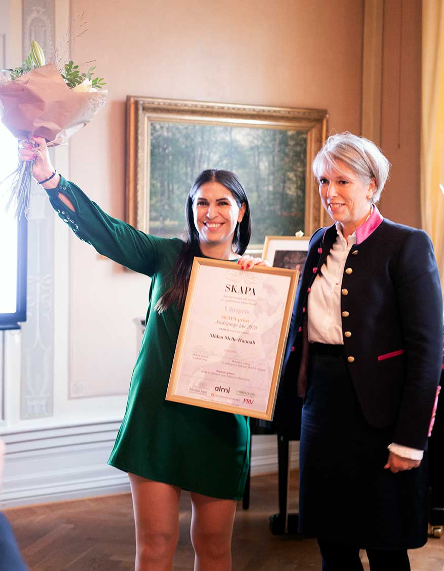 MIden Melle-Hannah jublar efter att ha tagit emot priset av landshövdingen Helena Jonsson