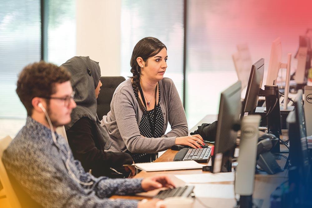 två kvinnor och en man sitter i datorsalsmiljö