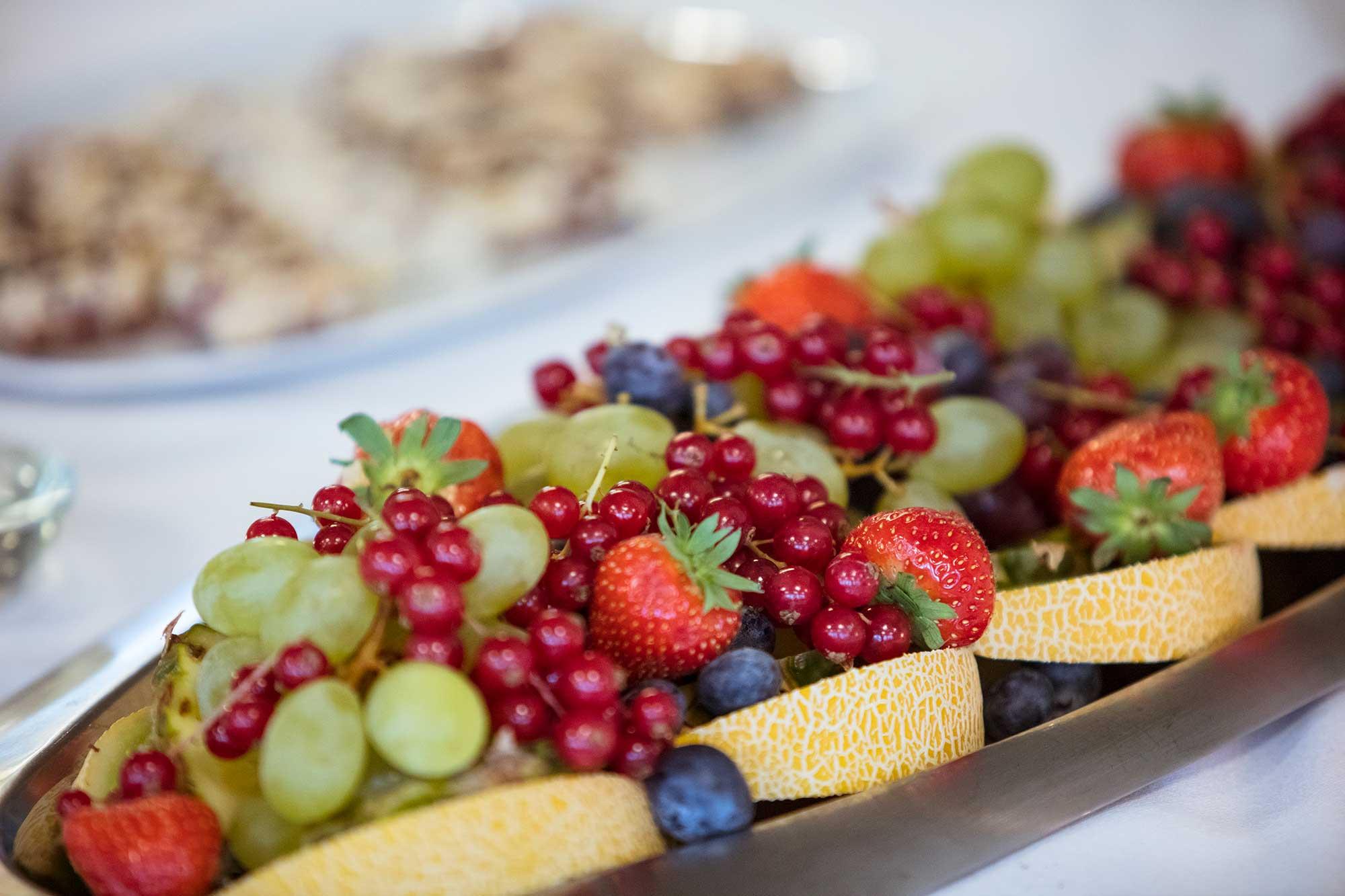 En fruktfat med melon, vindruvor, blåbär, jordgubbar och vinbär