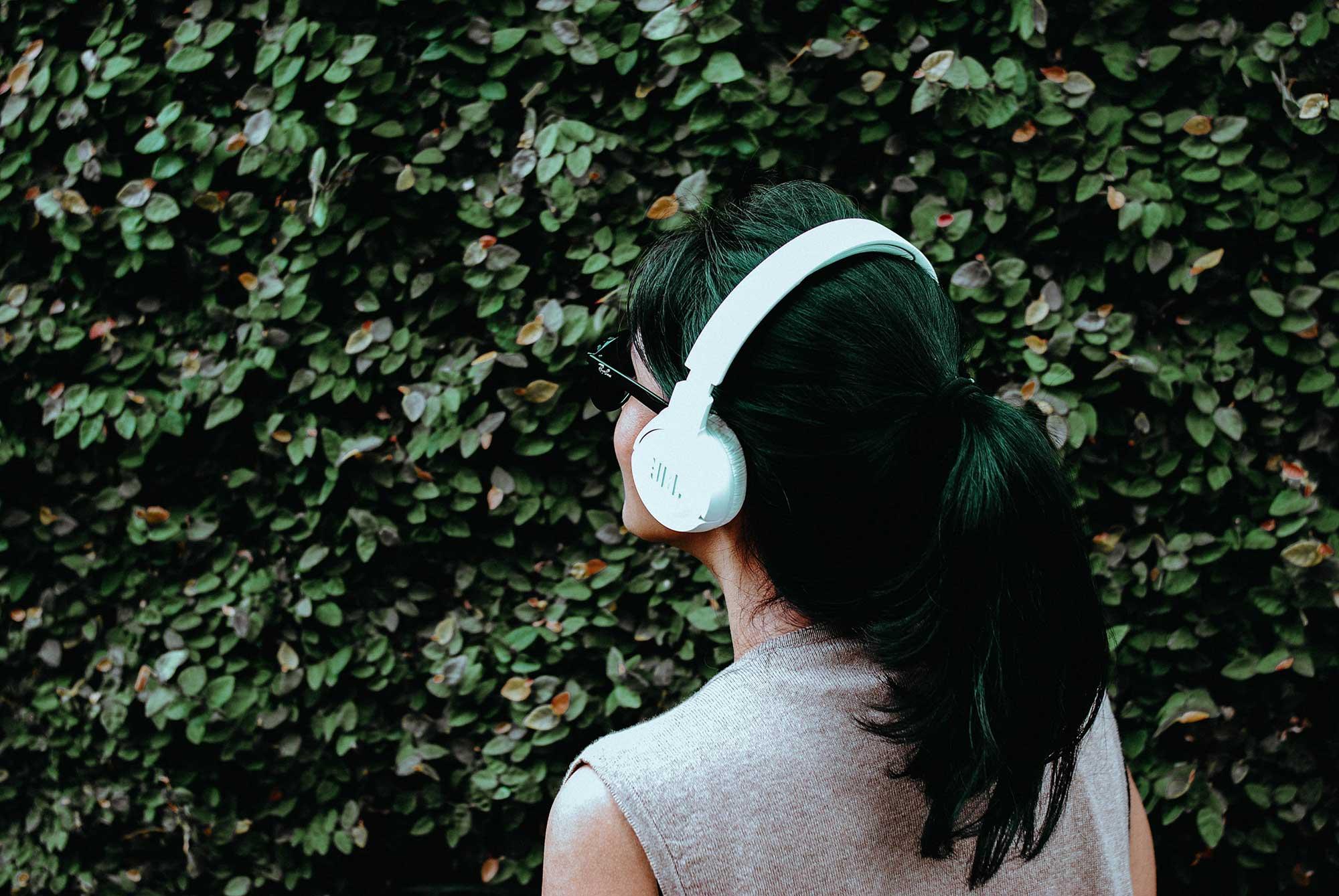 Person med uppsatt hår och stora hörlurar står framför en buske utomhus.