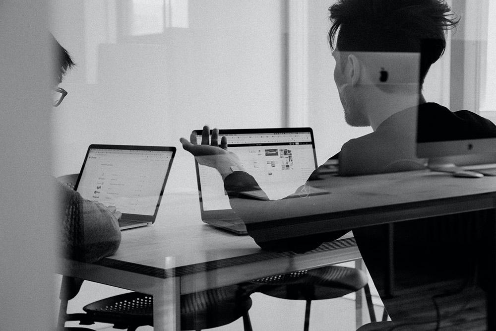 två killar som sitter med sina laptops i ett mötesrim