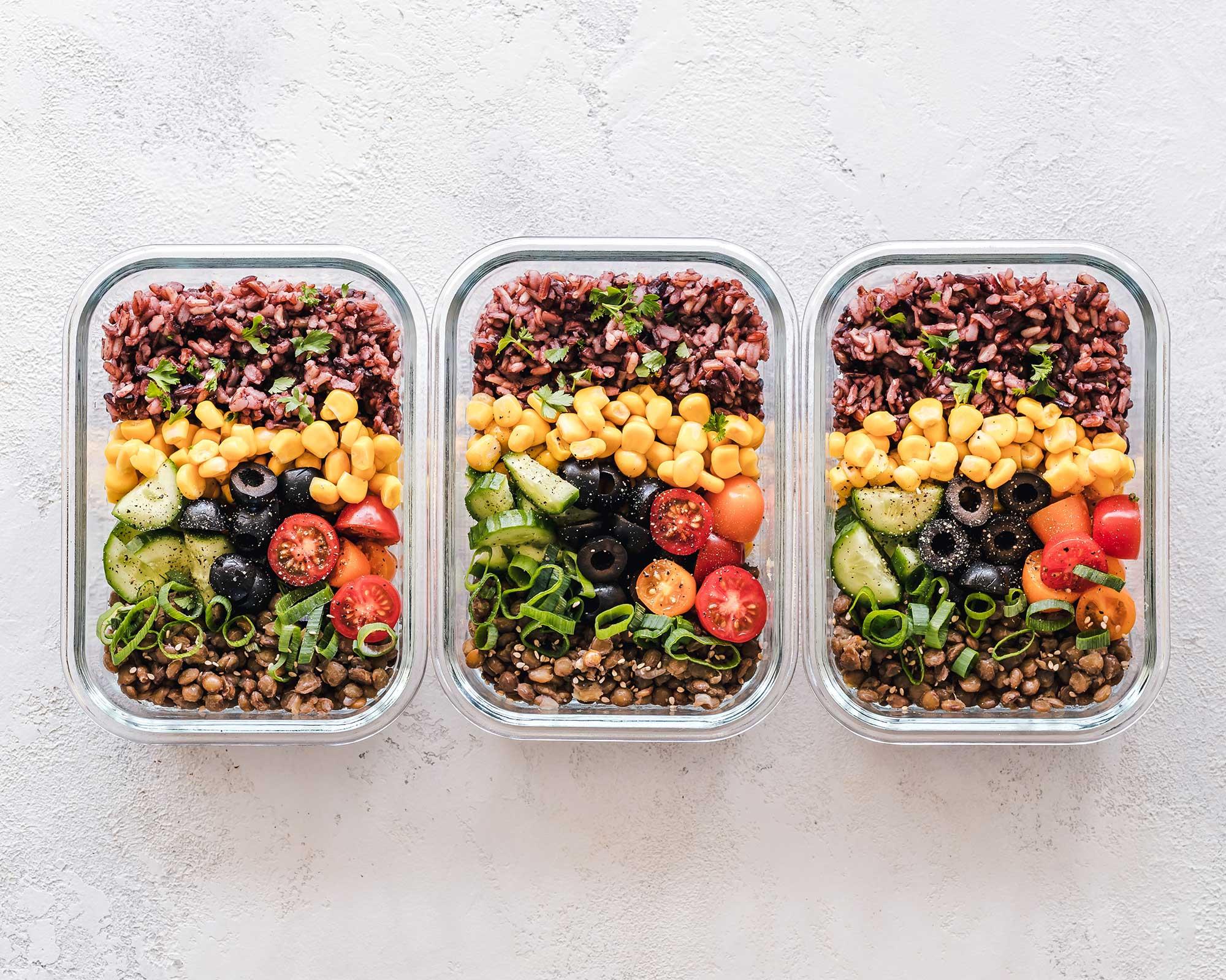 Tre matlådor fyllda med grönsaker på ett bord