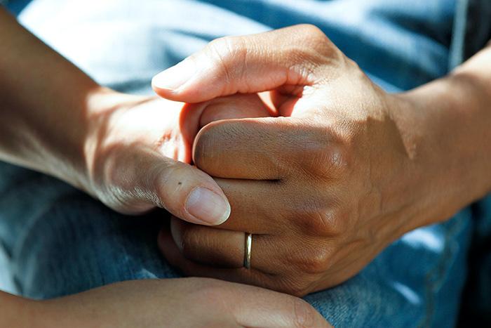 Närbild på två händer som håller i varandra i sjukhusmiljö