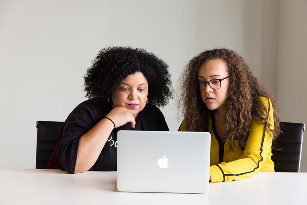 Två unga kvinnor arbetar tillsammans framför en laptop