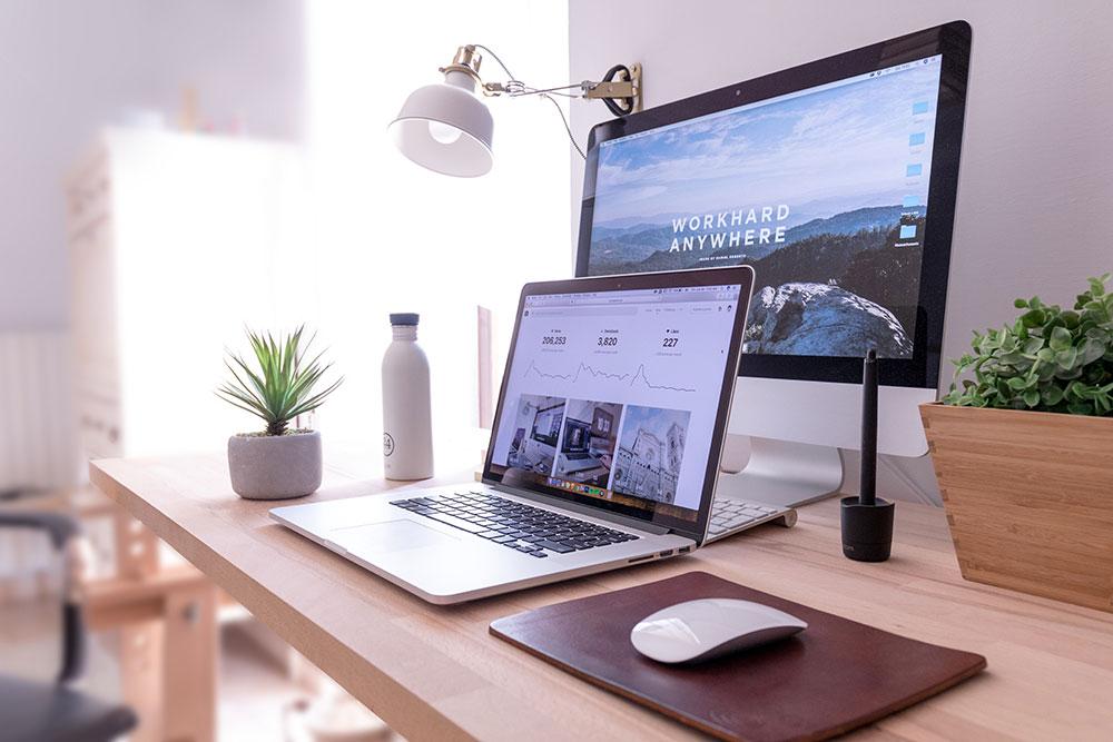 laptop, datorskärm och en vattenflaska på ett skrivbord i ett ljust rum