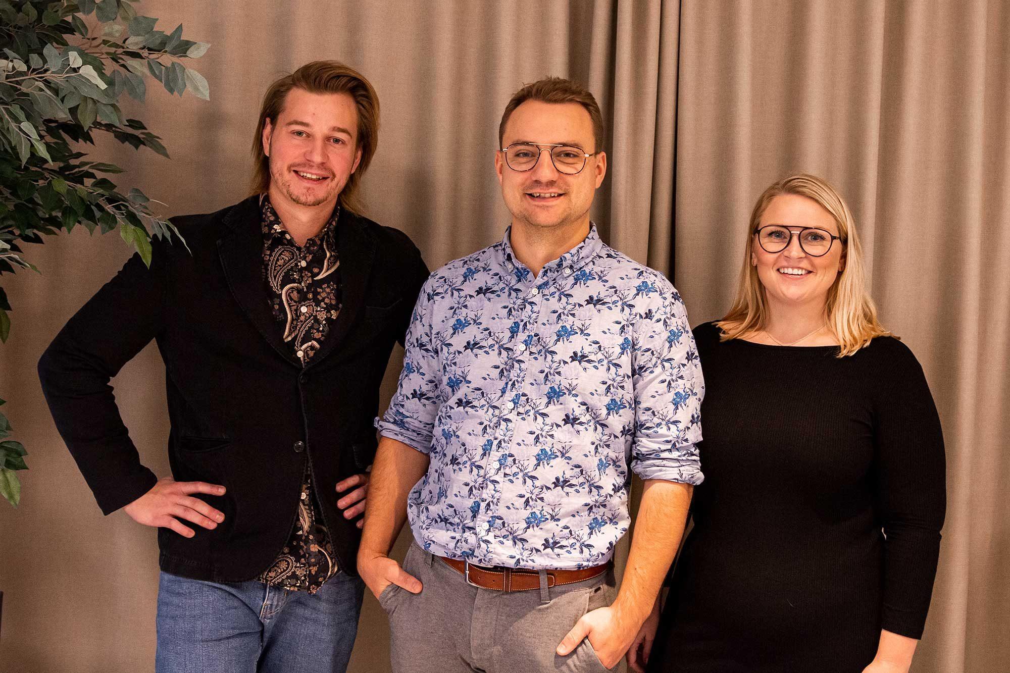 Erik Hermansson, Glenn Winbo Sondell och Ann Winbo står framför ett draperi.