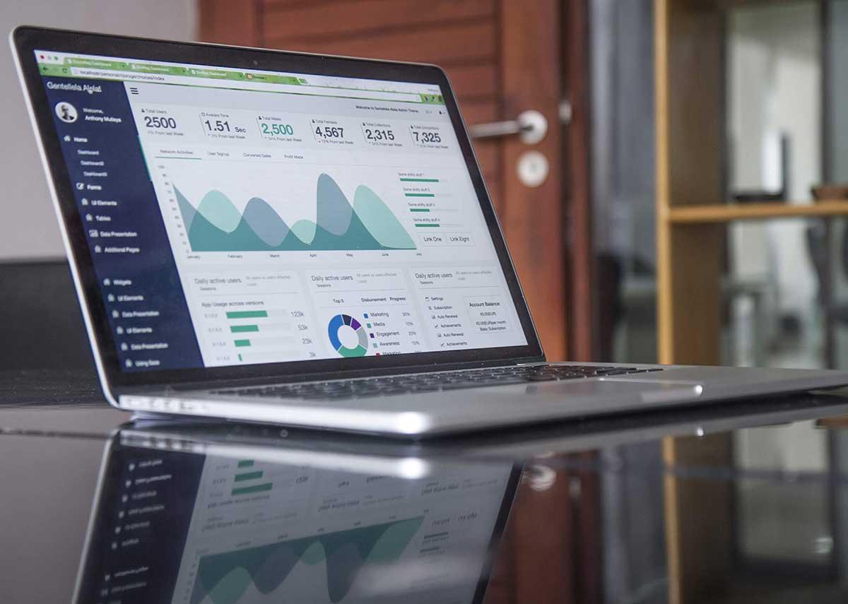 En laptop står uppfälld på ett bord och visar ett analysverktyg med statistik på skärmen