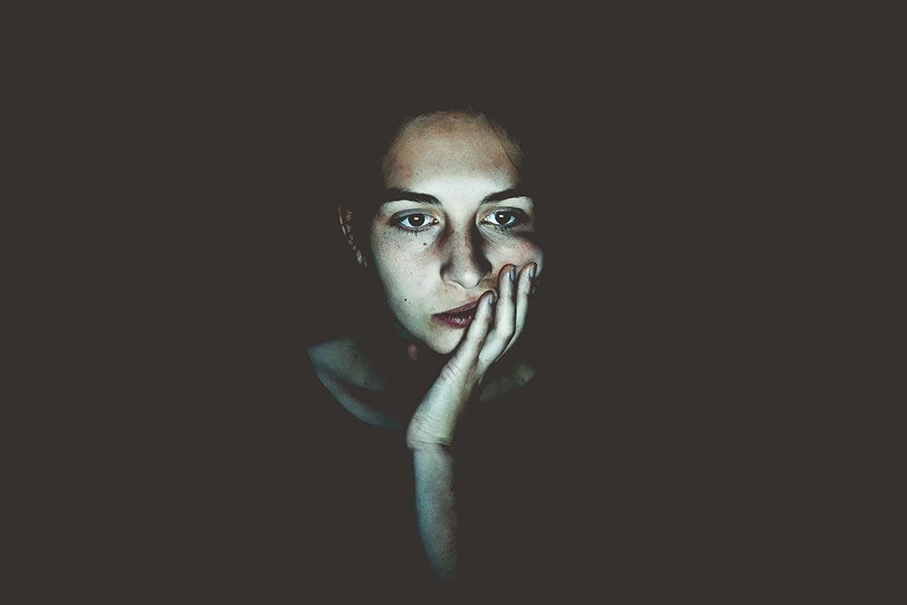 bekymrad kvinna i mörkt rum, som vilar ansiktet i händerna