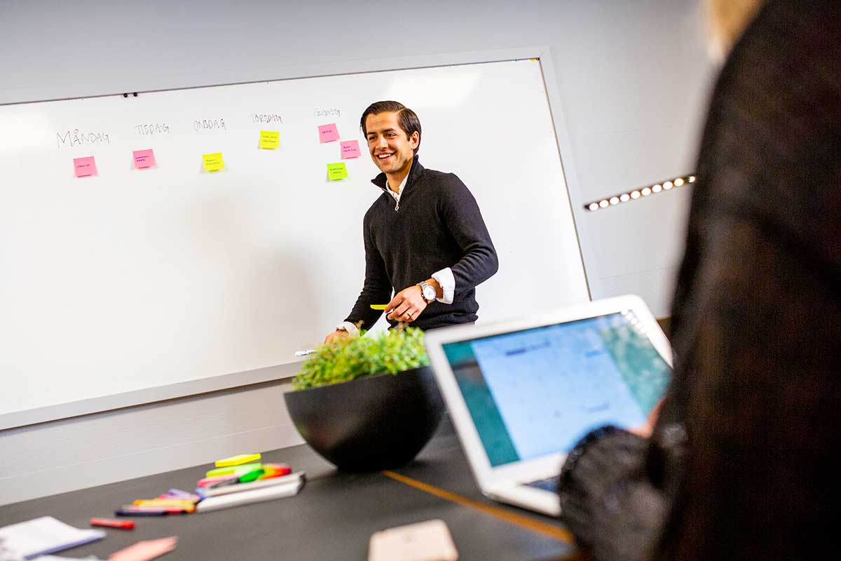 En leende person står framför en whiteboardtavla där det sitter olikafärgade postitlappar