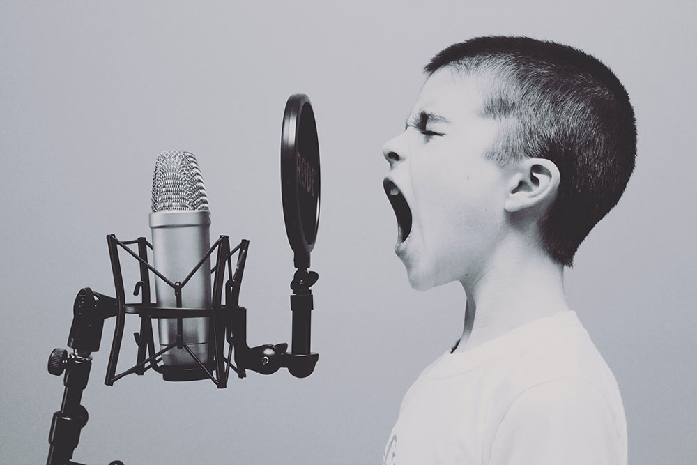 ett barn skriker in i en mikrofon