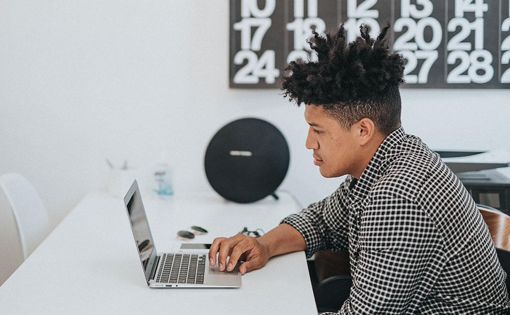 Kille med laptop i kontorsmiljö
