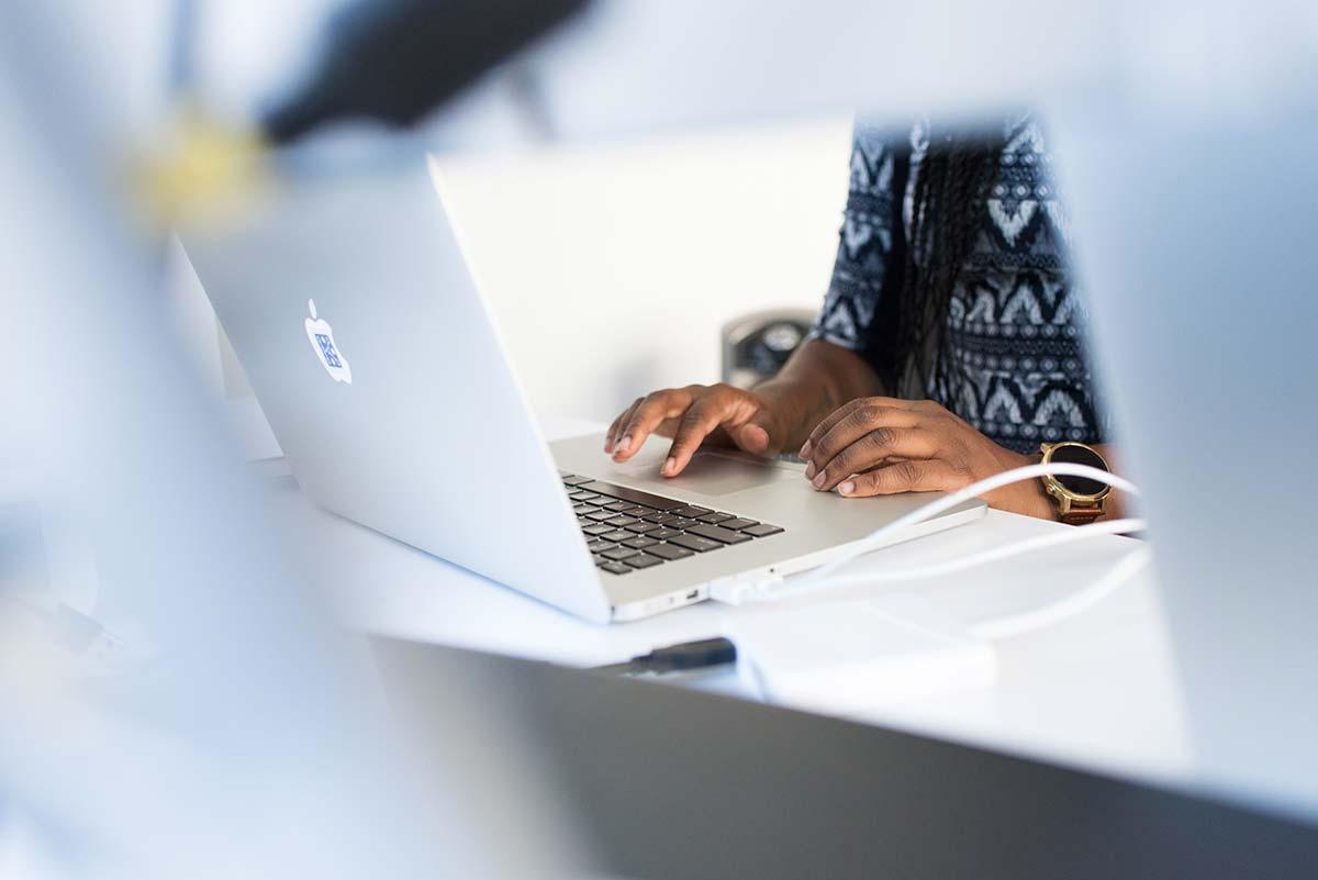 händer som skriver på en laptop