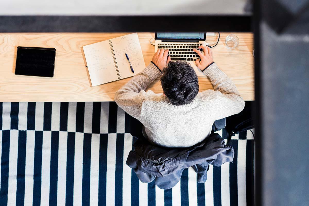 Skrivbord, man och dator i fågelperpektiv