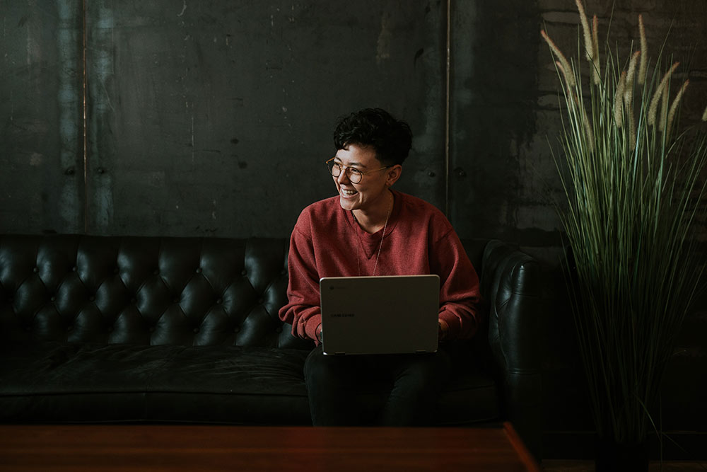 Glad tjej i soffa med dator i knät
