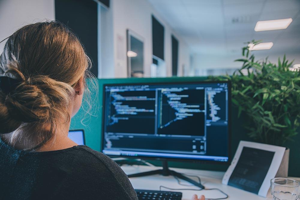 webbutvecklare framför dator med kod