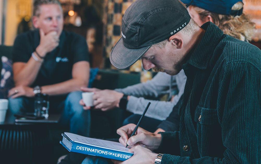 en man i loungemiljö skriver koncentrerat i sitt anteckningsblock