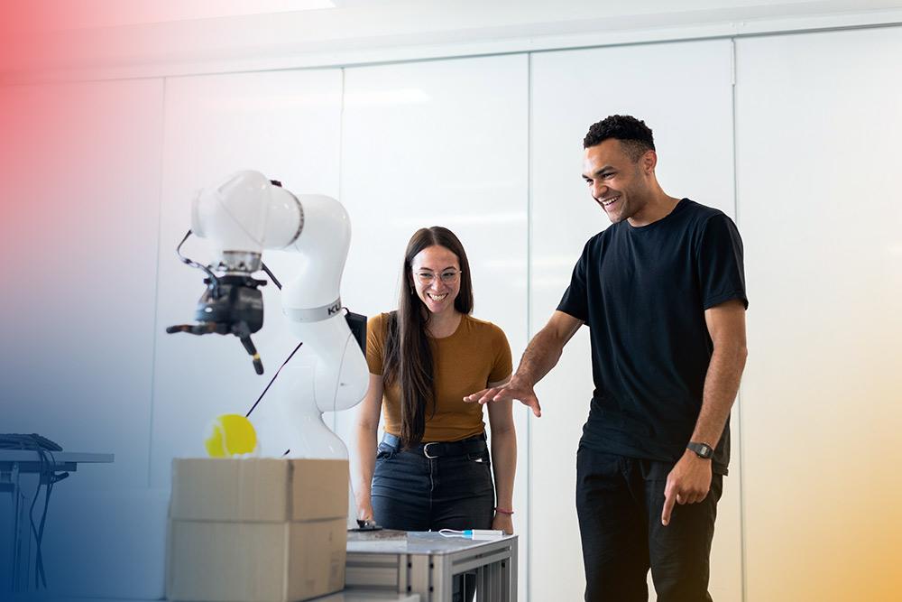 två glada ingenjörer studerar en robot