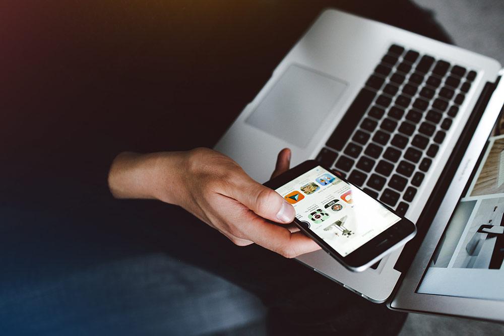 närbild på en laptop och en hand som håller i en mobiltelefon