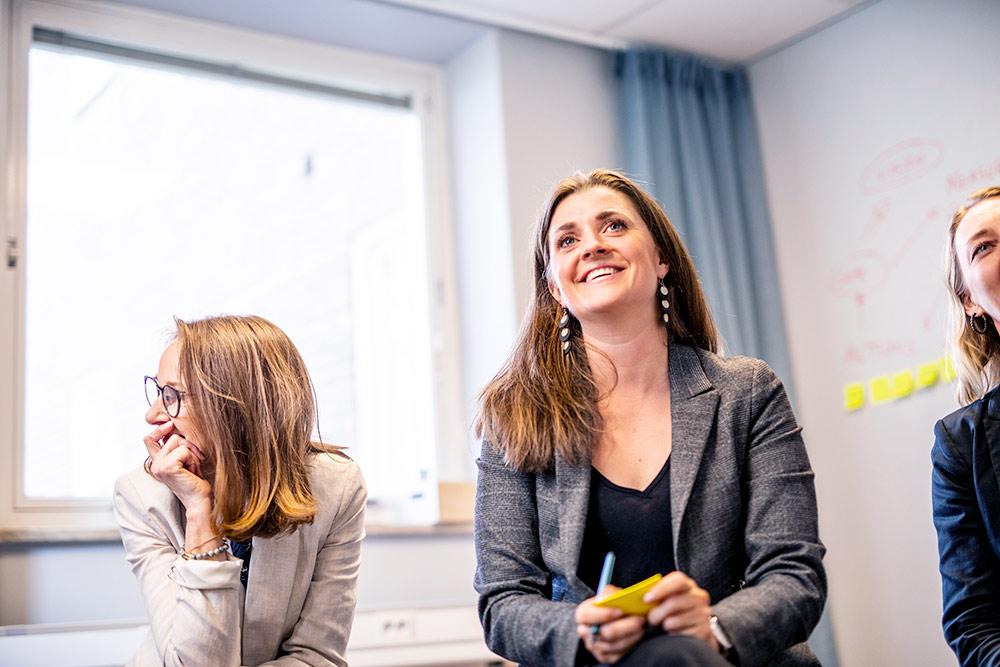 kollegor i mötesmiljö med postitlapp i handen