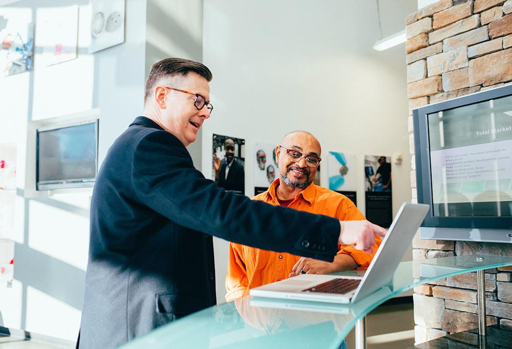 Två glada män som tittar och pekar på en laptop